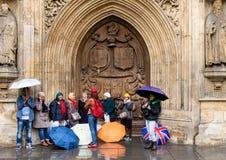 Turistas asiáticos que abrigan de la lluvia en el baño, Somerset, Reino Unido Foto de archivo libre de regalías