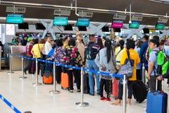 Turistas asiáticos que esperan en línea en la cabina del incorporar del aeropuerto fotografía de archivo