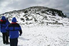 Turistas azules del abrigo esquimal que suben una colina Imágenes de archivo libres de regalías