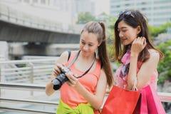 Turistas bonitos da mulher que olham a foto em sua câmera após o trave imagem de stock royalty free