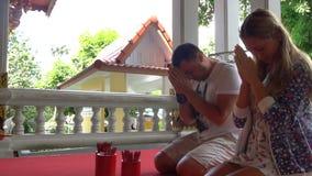 Turistas caucásicos que ruegan en el templo budista