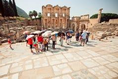 Turistas com os guarda-sóis que estão perto da biblioteca histórica de Celsus da cidade de Ephesus Fotografia de Stock