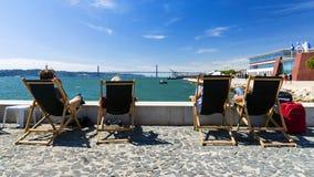 Turistas com os vadios do sol em Lisboa, na perspectiva de Foto de Stock