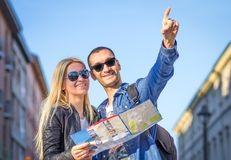 Turistas con el mapa de la ciudad Imágenes de archivo libres de regalías