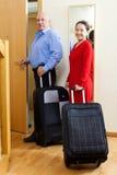 Turistas con equipaje cerca de la puerta en hogar Imágenes de archivo libres de regalías