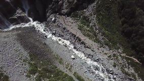 Turistas con la mochila que cruza el terreno rocoso con la hierba en el día soleado Opinión superior turistas en las montañas en  metrajes