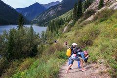Turistas con una cámara en la orilla de un lago de la montaña Fotografía de archivo