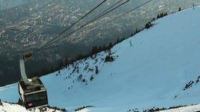 Turistas de elevación del teleférico moderno al funcionamiento de esquí, centro turístico de montaña almacen de video