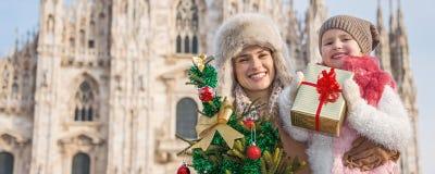 Turistas de la madre y del niño con el árbol de navidad y el regalo en Milán Imagen de archivo libre de regalías