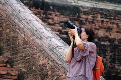Turistas de las mujeres que toman im?genes y el fondo ladrillo antiguo en el templo de Yai Chaimongkol, Tailandia foto de archivo