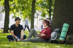 Turistas de los adolescentes con las mochilas en el parque en el mediodía del verano Fotografía de archivo