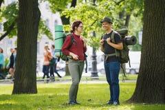 Turistas de los adolescentes con las mochilas que se colocan en el parque en el mediodía del verano Imagen de archivo