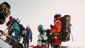 Turistas de los escaladores vestidos en un rato de la forma especial, del marcado en un lugar al lado de una roca y esperar la ca metrajes