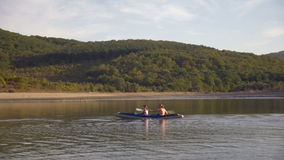 Turistas del agua de la familia que viajan en el río Dniéster La playa pintoresca, montaña demasiado grande para su edad con el b almacen de video