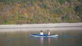 Turistas del agua de la familia que viajan en el río Dniéster La playa pintoresca, montaña demasiado grande para su edad con el b metrajes