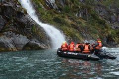Turistas del barco de cruceros cerca de las cascadas del glaciar Nena Fotos de archivo