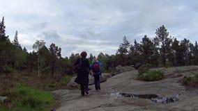 Turistas del caminante que suben el camino que lleva a la roca del púlpito de Preikestolen en Noruega