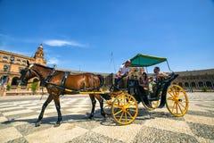 Turistas del carro del caballo que dan un paseo a través de la plaza de España en Sevilla imagen de archivo