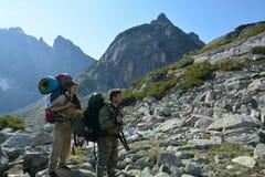 Turistas del hombre y de la mujer en las montañas Barguzinsky Ridge en el LAK Foto de archivo