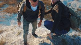 Turistas del trabajo en equipo vídeo de la cámara lenta amistad que camina para ayudarse a confiar en la silueta de la ayuda en m metrajes