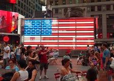 Turistas delante de una bandera americana electrónica en Times Square Imagen de archivo libre de regalías