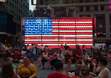 Turistas delante de una bandera americana electrónica en Times Square Foto de archivo libre de regalías