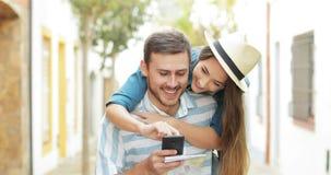 Turistas divertidos que bromean comprobando el teléfono de vacaciones almacen de video