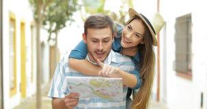 Turistas divertidos que bromean y que comprueban el mapa almacen de video