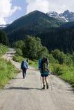 Turistas do Backpacker na estrada. Foto de Stock
