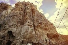 Turistas do explorador que cruzam um trajeto de madeira através das montanhas rochosas Fotos de Stock