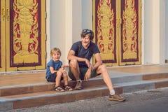 Turistas do pai e do filho no templo tailandês na cidade Wat Mongkolnimit de Phuket foto de stock royalty free