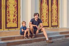 Turistas do pai e do filho no templo tailandês na cidade Wat Mongkolnimit de Phuket imagem de stock royalty free