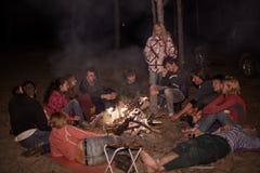 Turistas em torno da fogueira na noite Fotografia de Stock Royalty Free