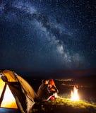Turistas en acampar en la noche contra el cielo estrellado imagen de archivo libre de regalías