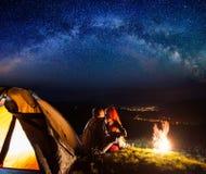Turistas en acampar en la noche contra el cielo estrellado foto de archivo