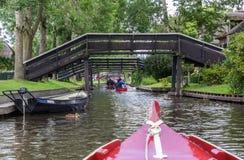 Turistas en botes pequeños debajo de los puentes de Giethoorn imagenes de archivo