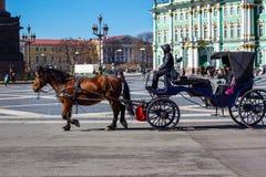 Turistas en carro en el cuadrado del palacio Foto de archivo