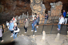 Turistas en cueva de la piedra caliza en Postojna Foto de archivo libre de regalías