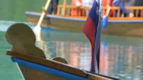 Turistas en el barco de fila en el lago sangrado metrajes