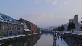 Turistas en el canal de Otaru con nieve en la estación del invierno