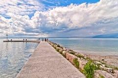 Turistas en el embarcadero con el cielo nublado en la orilla del este del lago Garda Imágenes de archivo libres de regalías