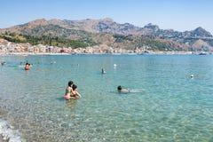Turistas en el mar jónico en la playa en Giardini Naxos Fotos de archivo libres de regalías