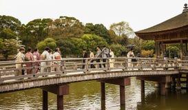 Turistas en el pabellón de madera sobre una charca Imagen de archivo libre de regalías