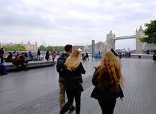 Turistas en el puente de la torre a lo largo del río Támesis Imagen de archivo