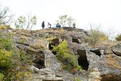 Turistas en la Chufut-col rizada medieval Crimea de la ciudad de las ruinas Imagenes de archivo