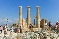 Turistas en la cima de ruinas antiguas de la acrópolis de Lindos Imagen de archivo libre de regalías