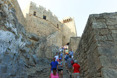 Turistas en la cima de ruinas antiguas de la acrópolis de Lindos Foto de archivo