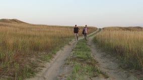Turistas en la naturaleza dos turistas van en el viaje de la naturaleza del camino con vídeo de la cámara lenta del viaje de las  metrajes
