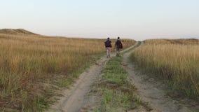 Turistas en la naturaleza dos turistas van en el viaje por carretera con vídeo de la cámara lenta de las mochilas del ` s de los  metrajes