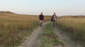 Turistas en la naturaleza los turistas del viaje dos van en el viaje de la naturaleza del camino con vídeo de la cámara lenta de  almacen de metraje de vídeo